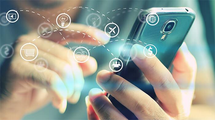 Een sfeerbeeld bestaande uit een close-up van een mobiele telefoon waar een persoon mee interacteert. Over de afbeelding heen zijn enkele iconen te zien als 'vliegtuig', 'play button', en 'dollar-teken'.